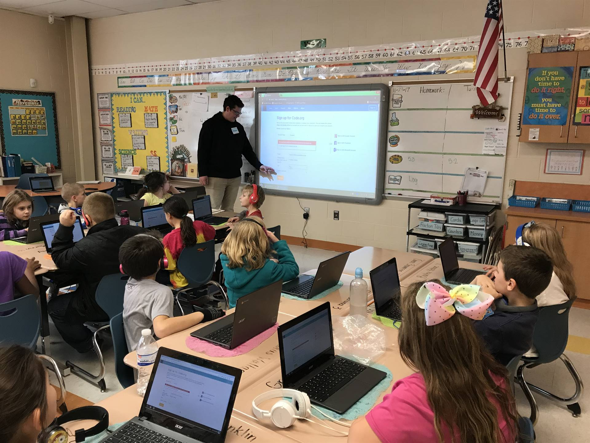 CHS student Franklin Vallant helps an elementary school student with a coding game.