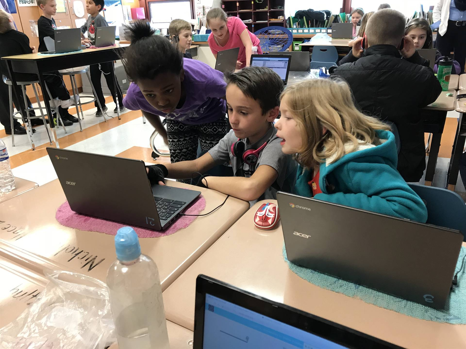 Senior Franklin Vallant assists a student with a coding activity.