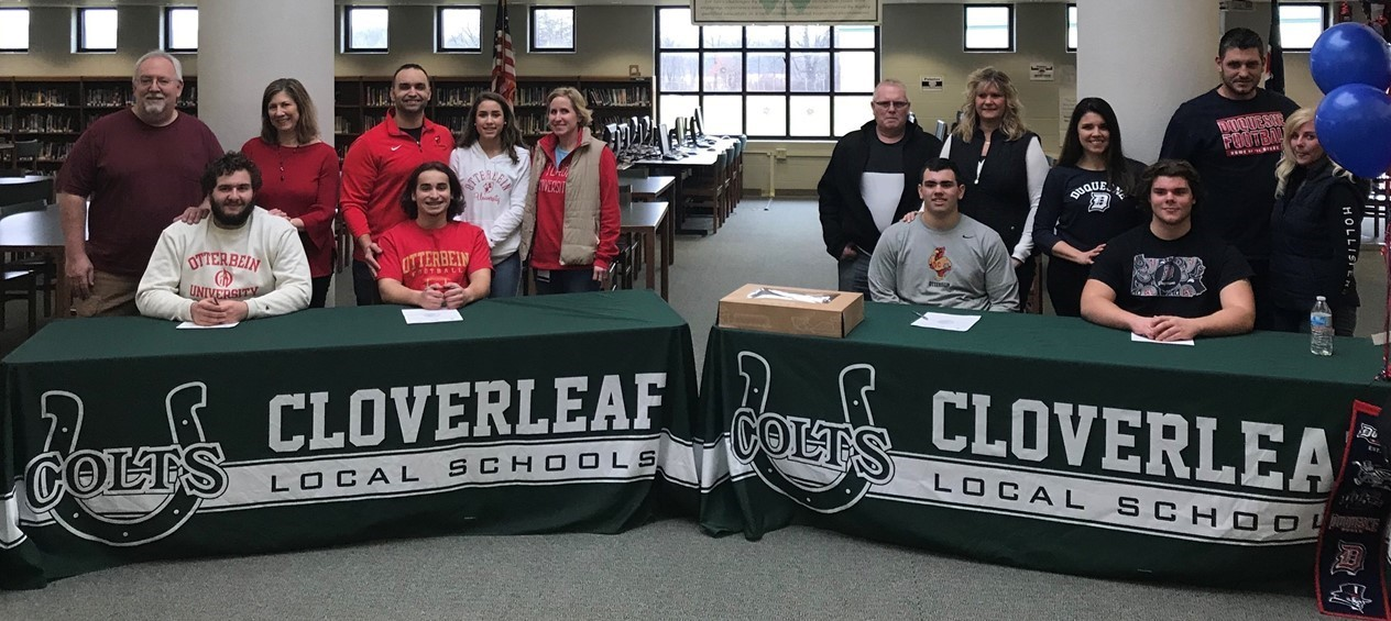 Cloverleaf football players are shown with their families as they sign their national letters of intent